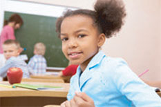 photo of young girl in classroom with other kids and teach in background